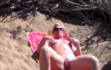 Blonde slut masturbates on nudist beach