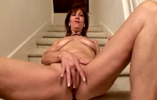 Mature woman Elle Denay masturbates on the stairs